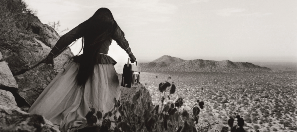A black-and-white photograph shows the back of a woman as she crests a rocky path above a vast desert landscape beneath an expansive sky. Her traditional, ethnic full skirt, long-sleeved blouse, and long, straight, dark hair contrasts with the modern portable stereo she carries.