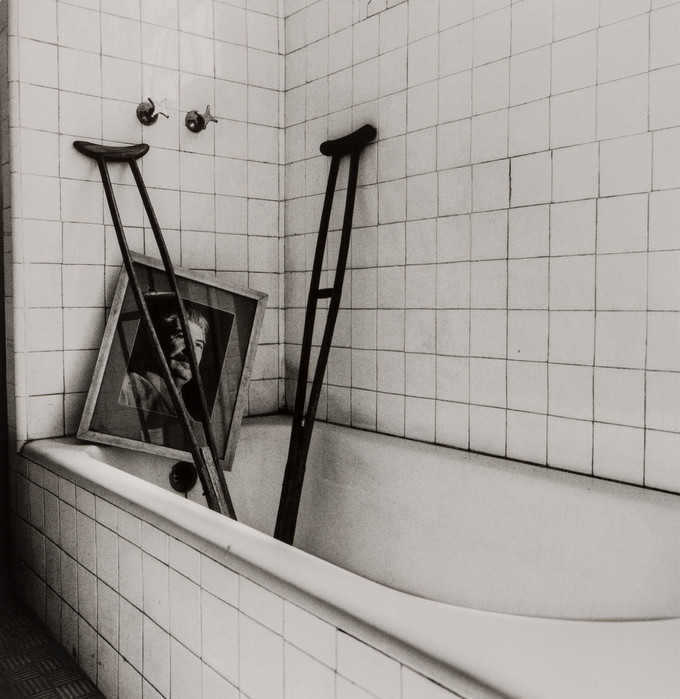 A black and white photograph of a white bathtub with a white tiled wall. In the bathtub are two wooden crutches leaning against the wall and a framed photograph of a middle-aged man with a dark mustache.