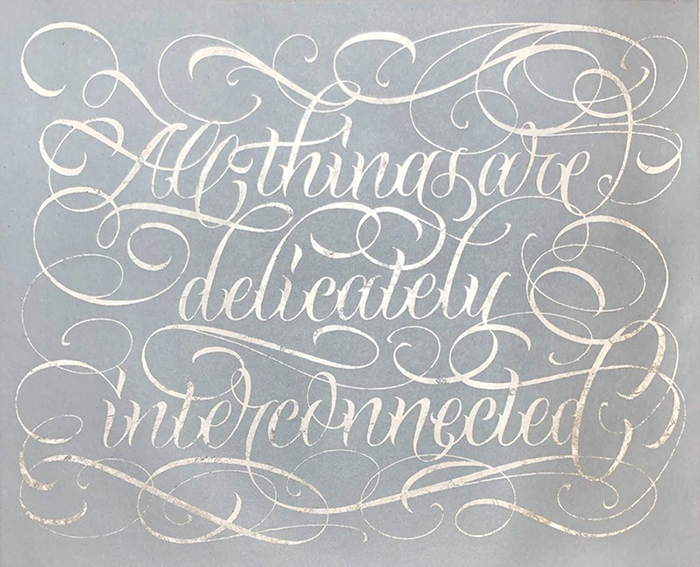 """A screenprint of the phrase """"All things are delicately interconnected"""" drawn in thin cursive script. The script is white against a very pale blue background; both colors have a textured, threadbare quality. Loops, swashes and swirls from the ends of letters fill the print."""