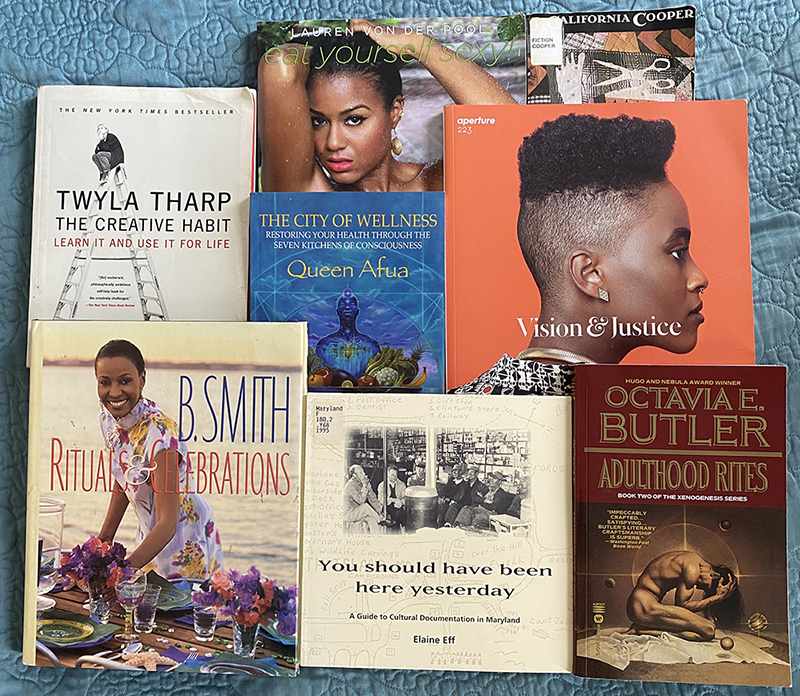 "A selection of eight books are arranged, covers facing up, on a blue blanket. The selection includes cookbooks, nonfiction, science fiction, books about spiritual wellness and creativity, and thick photography magazine titled ""Vision and Justice."""