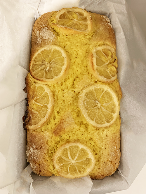 A close up photograph of a bright yellow cake loaf still resting in its parchment paper-covered baking tin. A few slightly caramelized lemon slices are baked into the porous top of the loaf and traces of a granulated sugar crust shimmer at the corners.