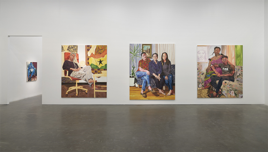 A photograph of a gallery space. Three large canvas paintings of people hang on the white wall directly across from the photographer; a smaller canvas is visible through an open doorway on the far left. The subjects of the paintings are seated in home environments.