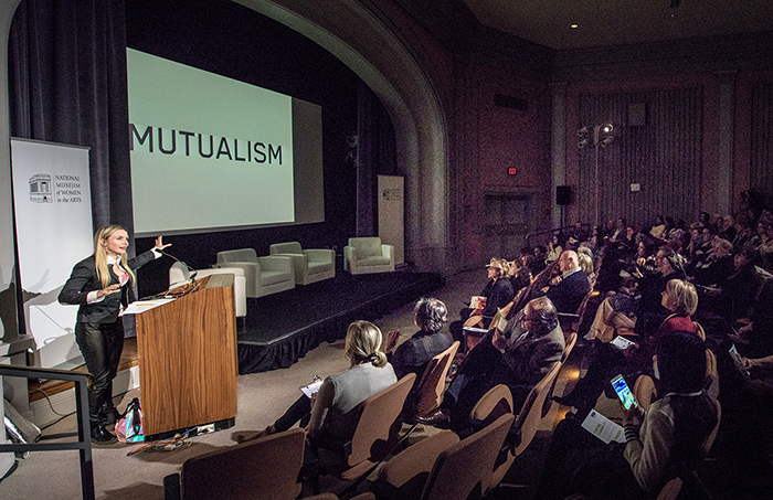 "A blonde woman stands at the podium in NMWA's performance hall, speaking in front of a packed audience. On the pull-down screen to her left, a slide with the word ""MUTUALISM"" in all caps in displayed."