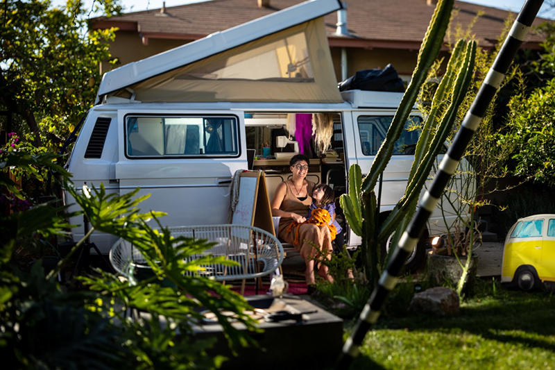 A photograph of a woman seated in the side door of her camper van next to her small daughter, who looks up at her. Lush green trees, bushes and cacti surround the vehicle, which is parked between her house and lawn. A children's easel is set up on the ground beside the woman.