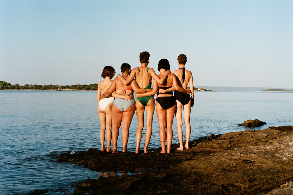A color photograph of a group of five young girls from behind. They wear bathing suits and stand on a rocky shoreline, looking out to a calm sea with their arms around each other. A lush green coastline is visible in the background.