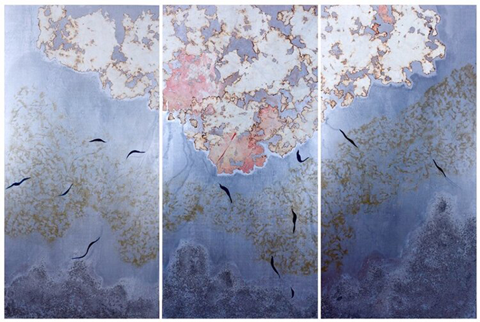 Cloud-like motifs stretch across three vertical panels: a speckled dark blue pattern rises from the bottom, an organic gold pattern spans the middle, and a bleached pattern with red and burnt orange explodes at the top. Shapes of silhouetted birds mark the middle of each panel.