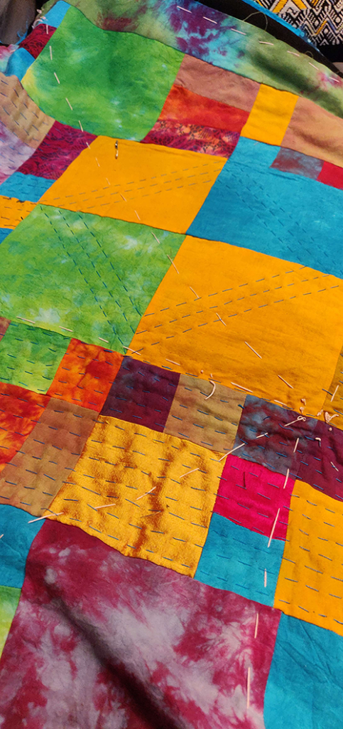 A photograph of an in-progress, hand-stitched quilt, made from bright, vibrant colors including yellow, green, blue, pink, and red. Some squares appear tie-dyed, others are solid.