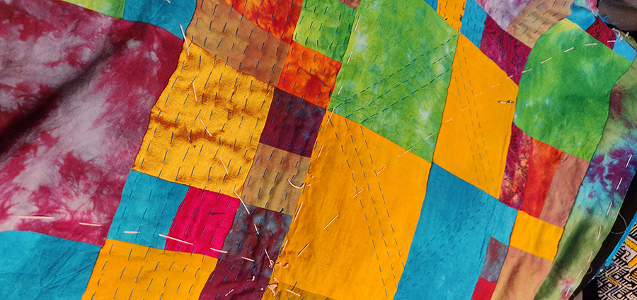 A close-up image of a color block quilt, taken diagonally. Colors repeat throughout without a set pattern. A golden yellow is the predominant color, but there are also lush light green, aqua, magenta, and tan blocks; some blocks look to be tie-dyed in multiple colors.
