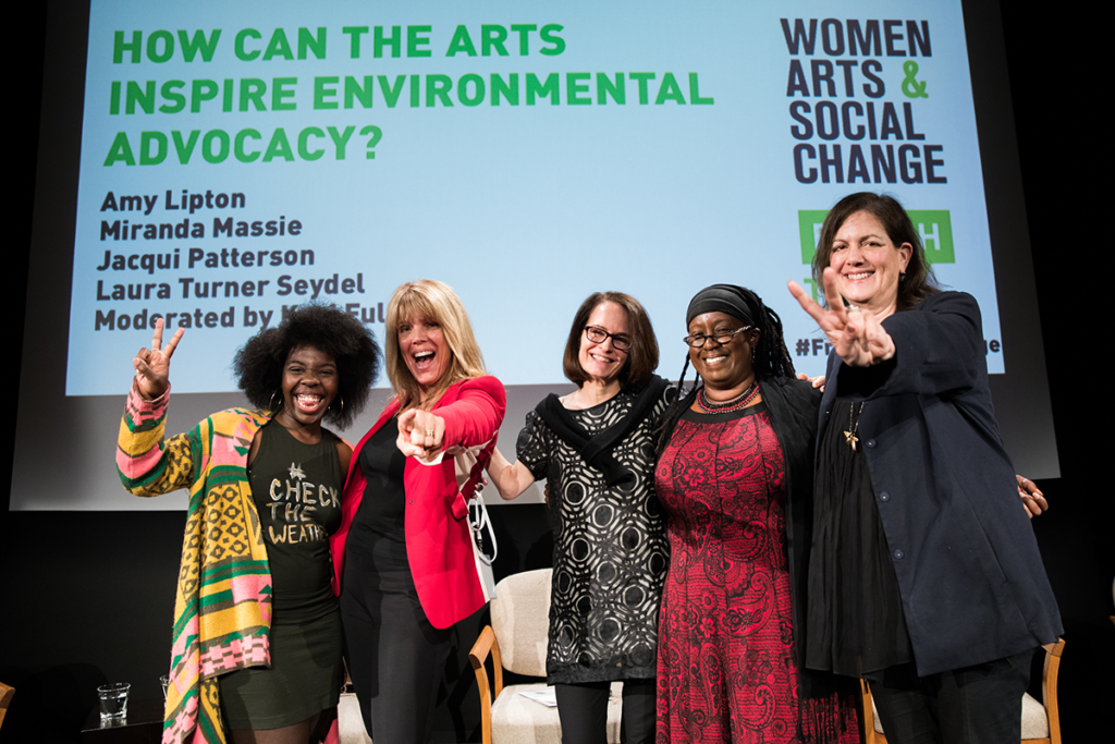 "Five diverse women pose happily in NMWA's performance hall, in front of a projected slide that says ""How can the arts inspire environmental advocacy?"" They smile wide, one woman points happily at the camera, and another throws up a peace sign."