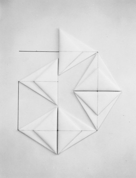 Six folded white triangles resembling origami form a large geometric shape on a white background. Connected by a continuous line that bisects their center, the corners of each triangle touch and encourage the eye to move in a circular fashion.
