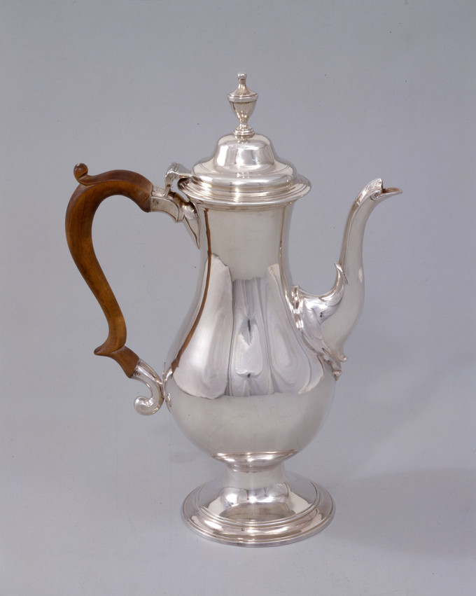 Silver coffee pot features a tall, baluster-shaped body, swan-neck spout, and a wooden scroll handle. In keeping with the Neoclassical style, the pot is smooth, simple and relatively unadorned.