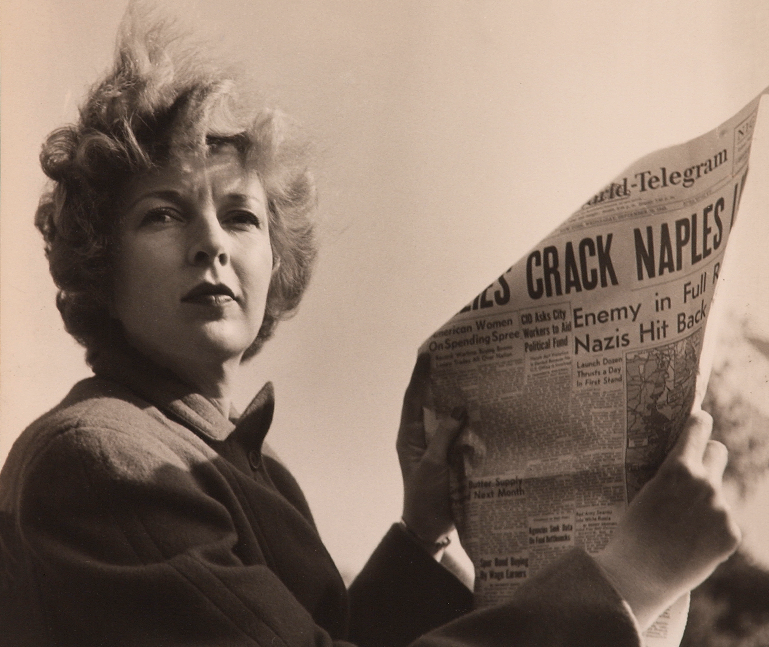 A black-and-white photograph of a light-skinned adult woman holding a newspaper with news about World War II. She wears a coat and her short, curly hair is caught in the wind.