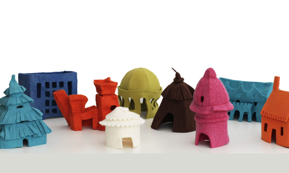 Arrangement of nine felt structures in multiple colors and a variety of shapes sitting on a white table