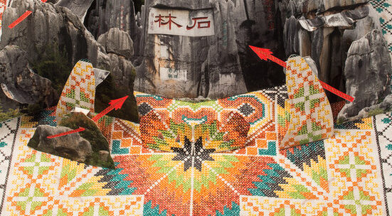 Large-scale pop-up book with a group of limestone formations resembling weathered tree trunks sits on top of a hand-embroidered base of colorful geometric patterns that repeat in abstract shapes over the center of the piece. A crescent moon and single star peek from behind.