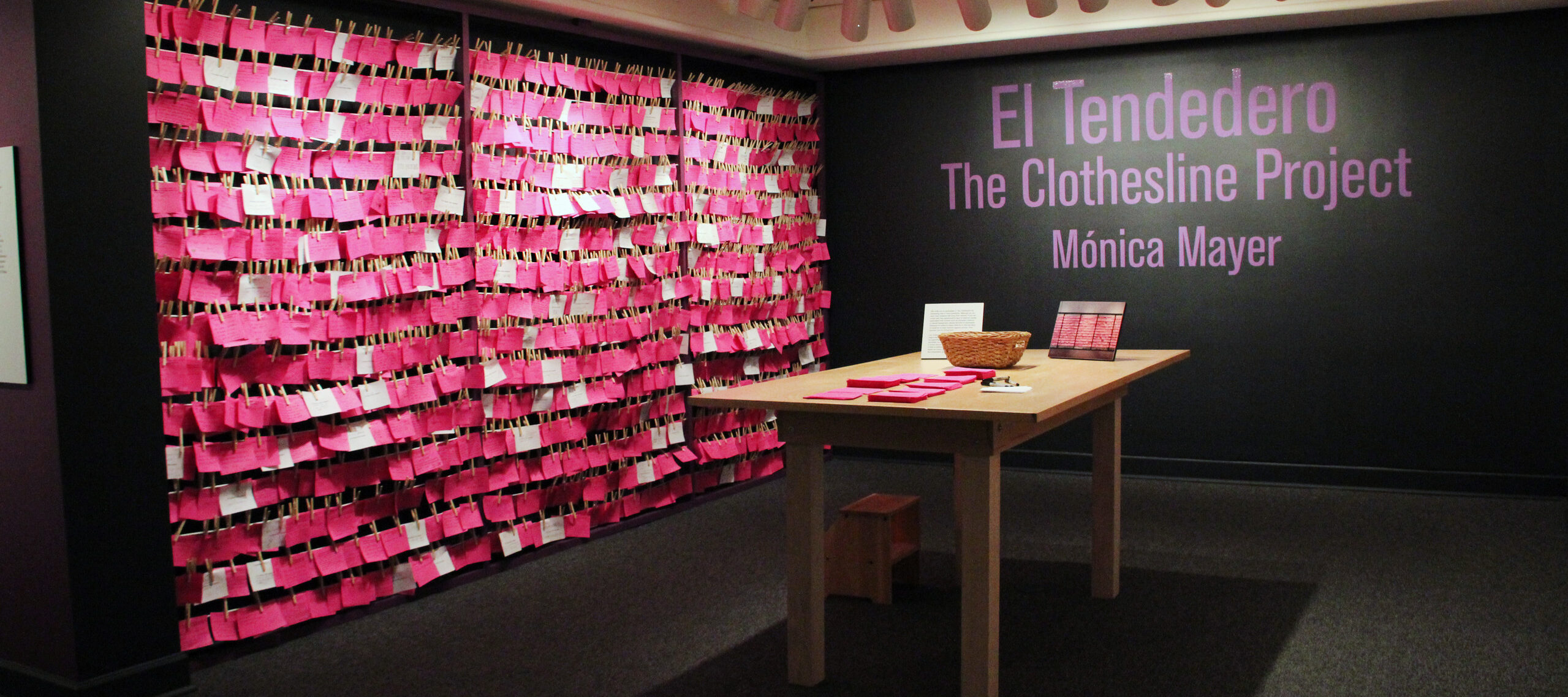 View of exhibition gallery features bright pink post-it notes line the wall from ceiling to floor. On the adjacent wall are the words in pink text: