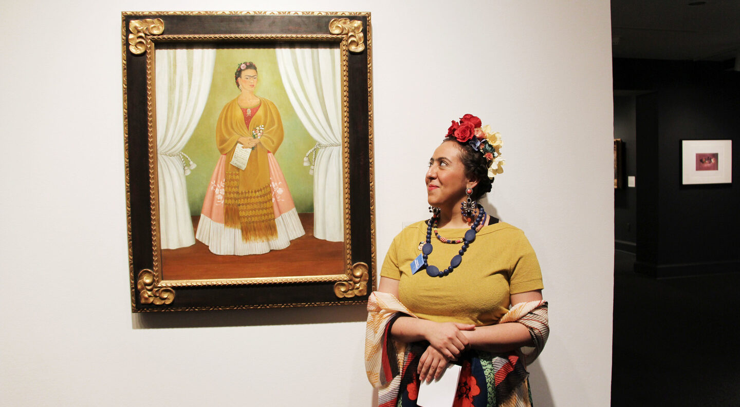 A medium skin toned woman in a yellow top and brightly patterned long skirt with flowers in her hair looks to her right at a painting of a similarly dressed woman.