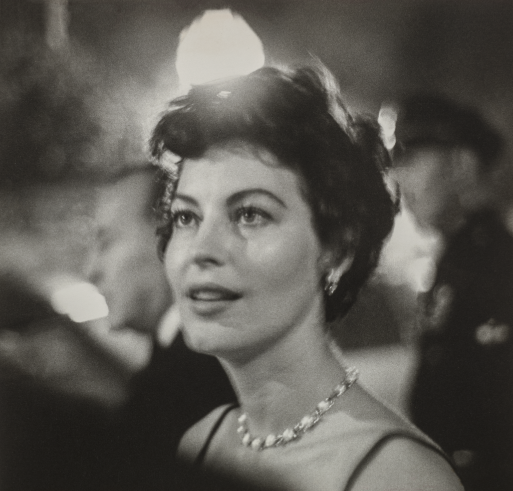 Ava Gardner, a woman with light skin tone and wavy, short brown hair, is shown from the shoulders up. She wears a jeweled necklace and is surrounded by lights and people at a party. She looks to the side of the camera at something out of frame with a fixed gaze and slight smile.