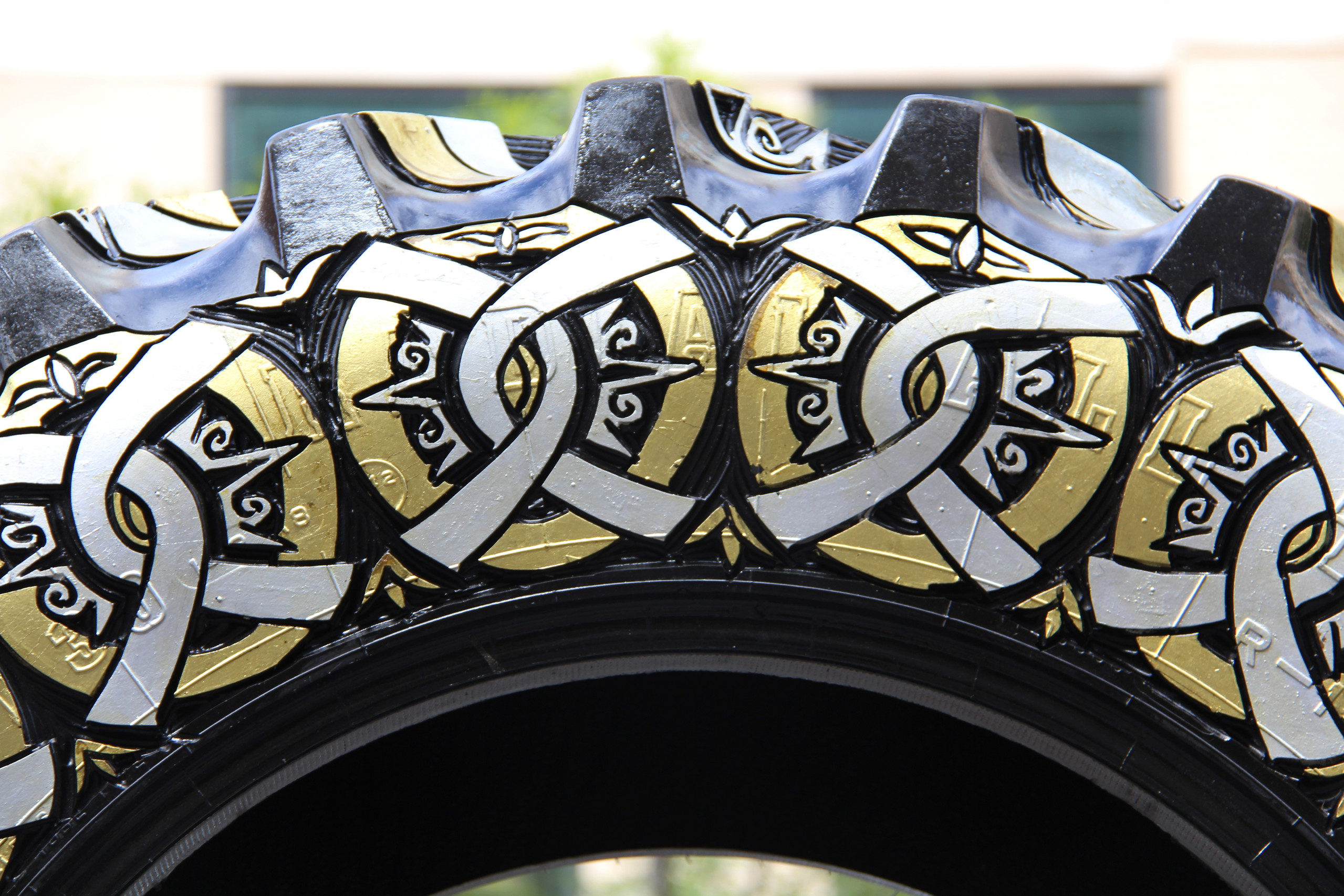 Close-up photograph of a sculpture made of a truck tire carved with circular designs and painted gold and silver