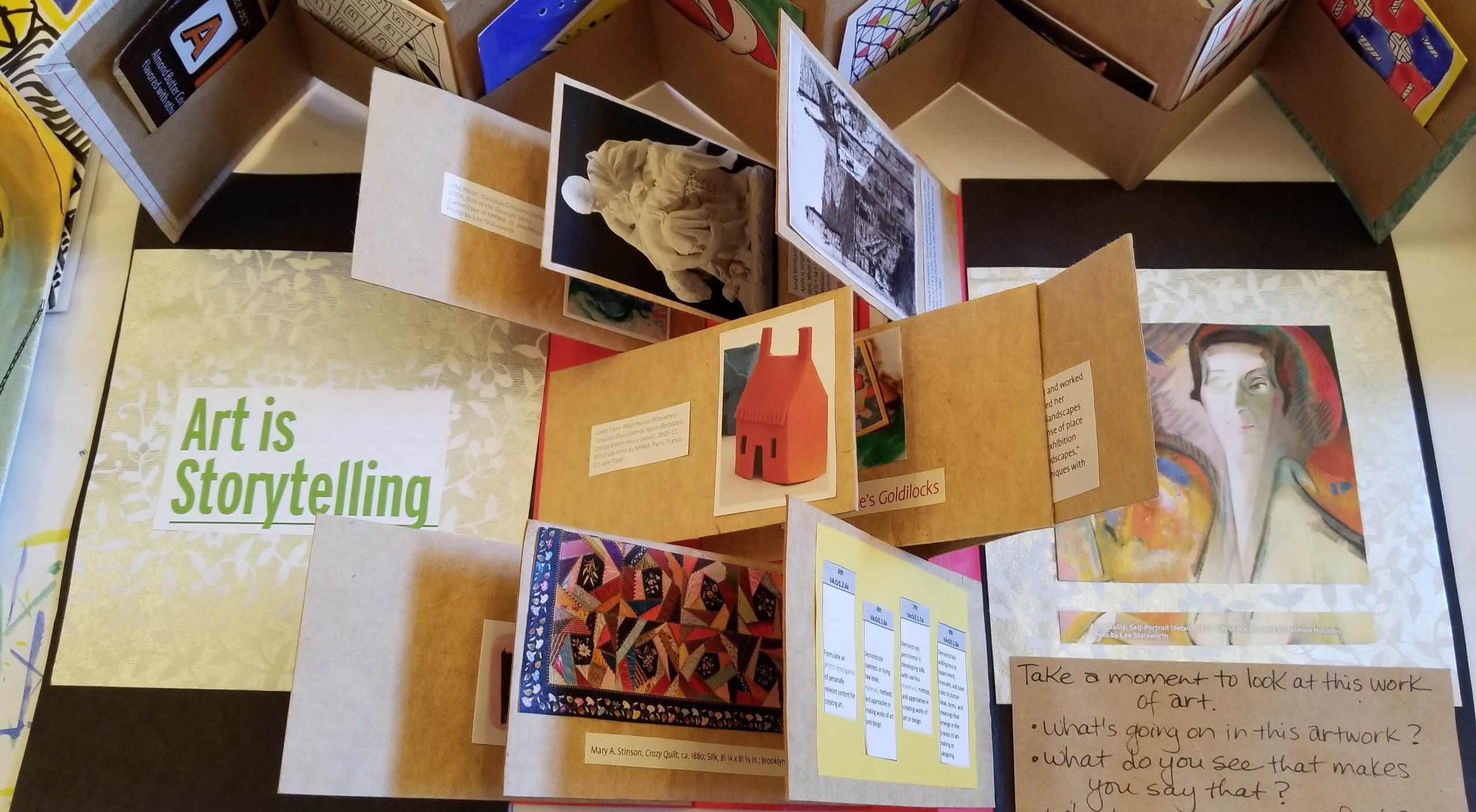 A birds-eyed view of a display of artists books showing a variety of folded paper and works of art.