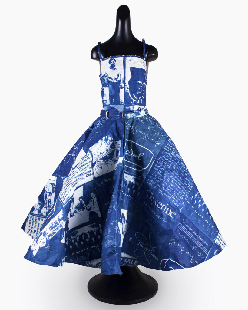 A sleeveless rich blue full-length gown placed on a headless black mannequin with rounded base. The dress has white text and images printed on the surface.