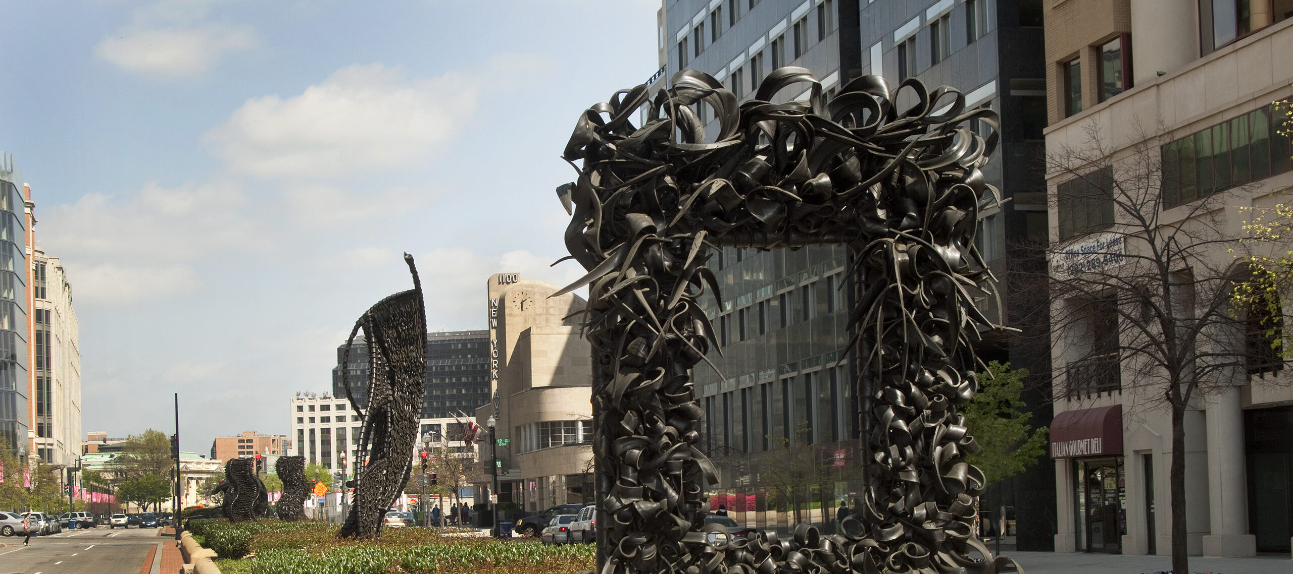 """A large metal sculpture stands in the middle of the street, similar to an empty rectangular picture frame. The """"frame"""" is crowded with undulating, coiling metal sculptural elements that occasionally end in spikes. Behind stand three vertical twisting, net-like metal sculptures."""