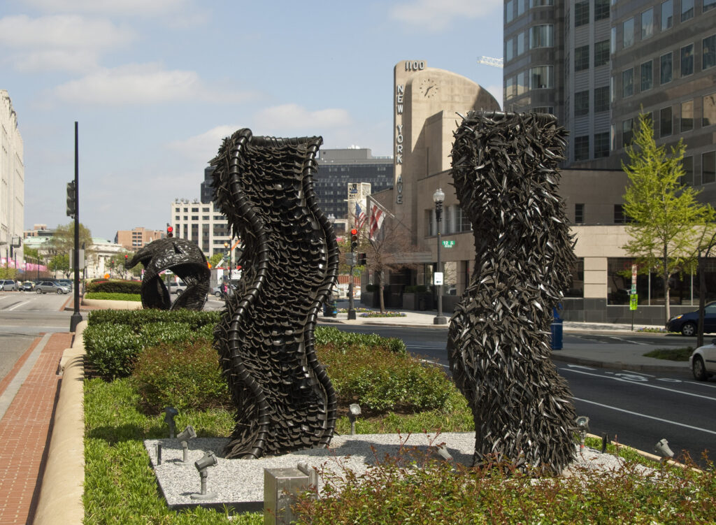 Two large abstract sculptures made from tires rise from a center median in a city street. The sculptures are wavy columns.