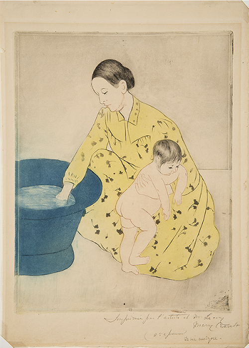 A woman, centered in the frame, crouches by an indigo-colored basin to the left. She is enveloped in a long-sleeved, collared yellow dress with black floral motifs. Looking into the water, she reaches her right hand into the basin, while bracing a naked infant with her left arm.