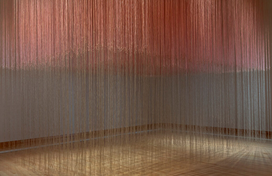 Strings of pale pink linen hang from the ceiling of a grey gallery room. The strings are more densely concentrated halfway up; this top layer is more clearly pink, while the strings hanging below are sparse and fainter. The organization of the strings evokes clouds and rain.