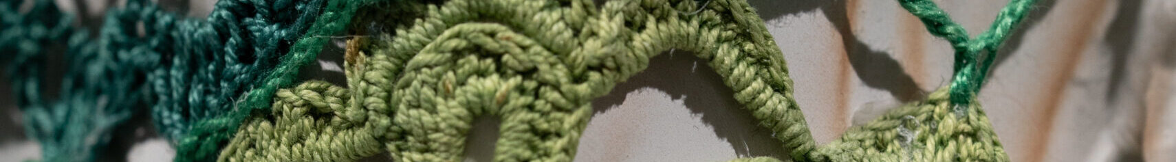 Close-up detail of a larger artwork shows an off-white ceramic surface that is covered by panels of crocheted yarn in emerald and citron green.