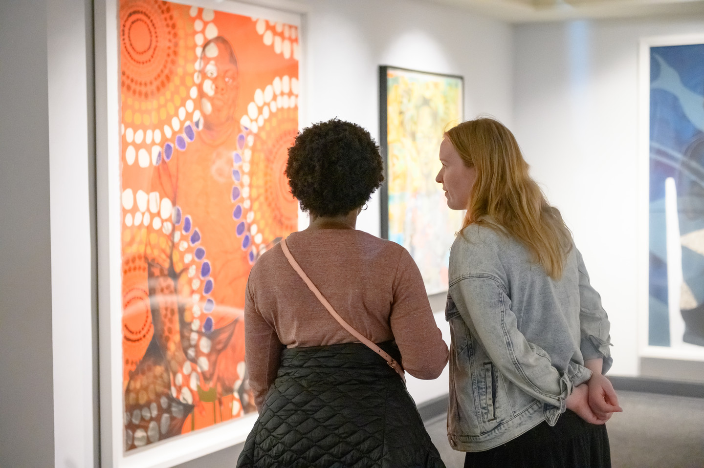 Two figures stand facing a large colorful work on paper. The figure on the left is dark skinned with short, curly, brown hair, the figure on the right is light skinned with long, straight, blonde hair. The work on paper depicts a seated dark skin person staring confidently at the viewer; an overlay of bright orange and circular patterns of white, blue, and brown circles covers the person and background.