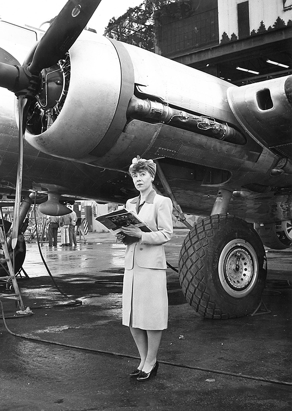 A black and white photograph of a light-skinned woman standing in an air field in front of a parked plane. She wears a blazer with shoulder pads, a knee-length skirt, black heels, and a headscarf. She cradles a large stack of papers; her pensive gaze is aimed up and to her left.