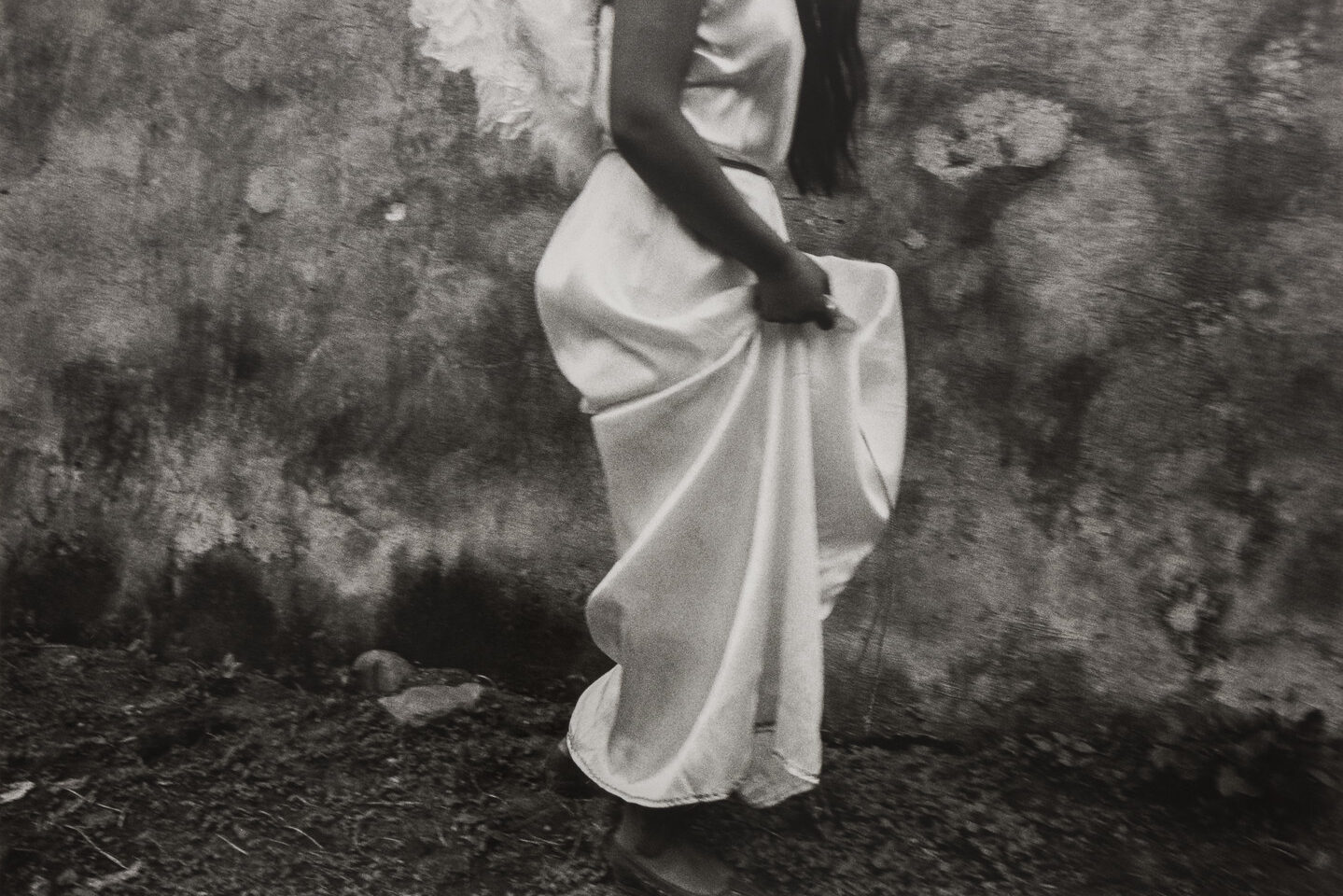 A black-and-white photograph of a woman in profile from the shoulders down with feathery white wings on her back walking and hoisting up her silky white dress.