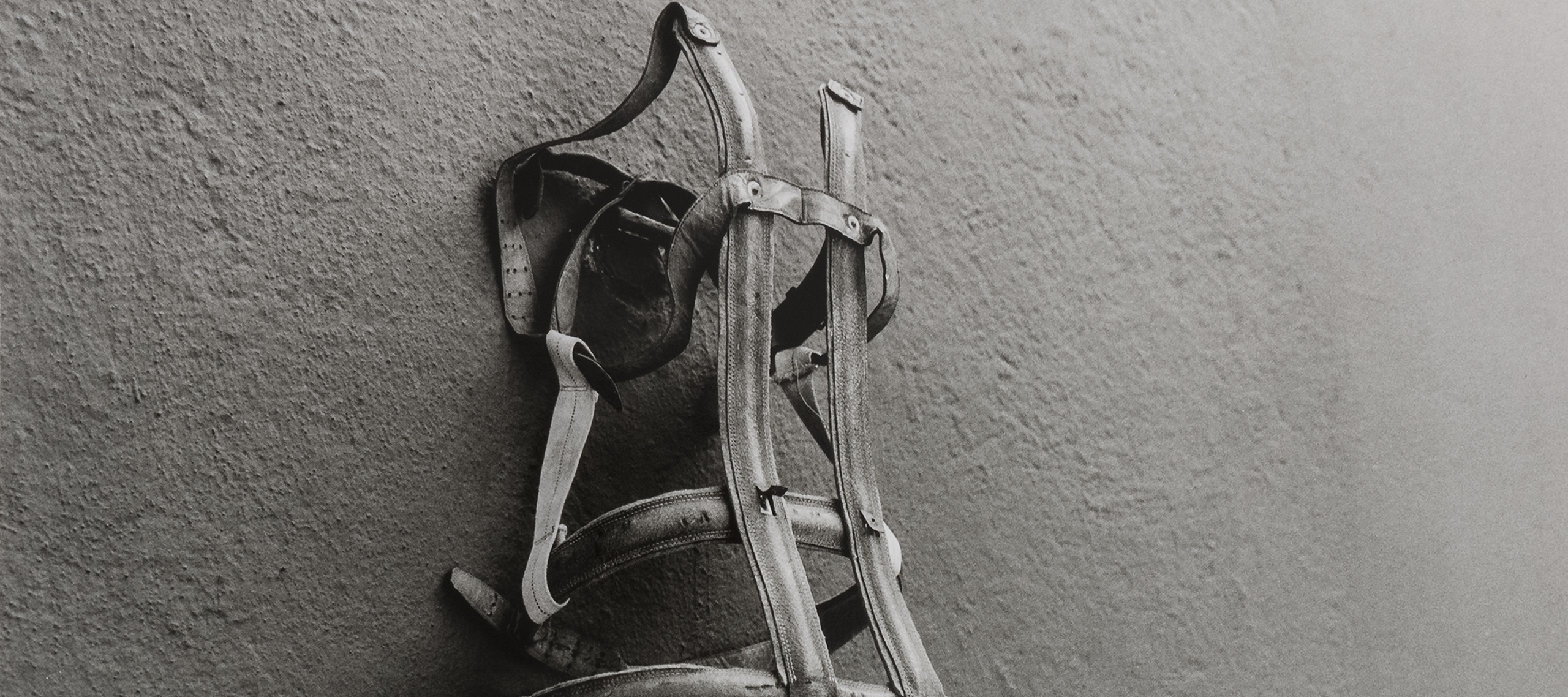 A black and white photograph of a worn body brace pinned on a blank concrete wall. The photograph is taken from slightly below and to the left of the brace. Similar to a corset, the brace itself is simultaneously lonely, foreboding, and empty as it hangs.