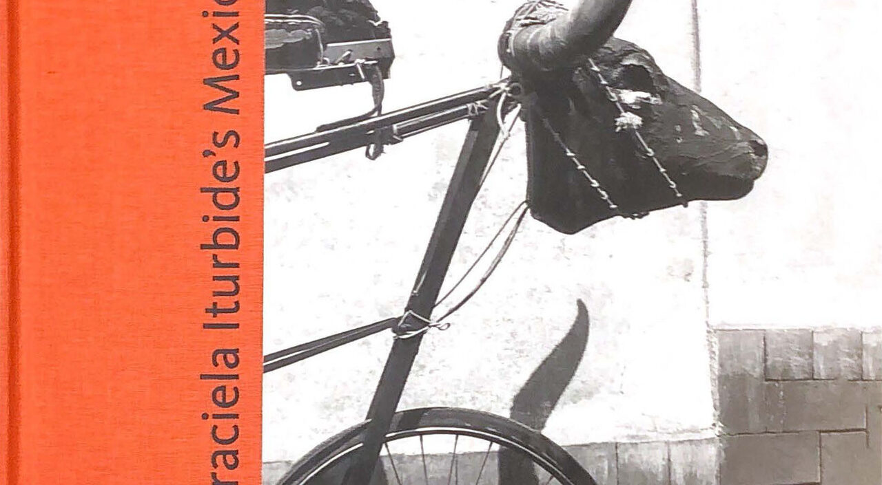 Cover of the exhibition catalogue titled 'Gracieal Iturbide's Mexico' shows a black and white photo of the front of a bicycle with an animal scull and horns in place of handlebars.