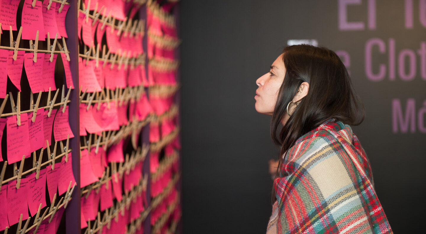 A light-skinned woman with dark hair looks at a wall of bright pink notes hung on multiple rows.