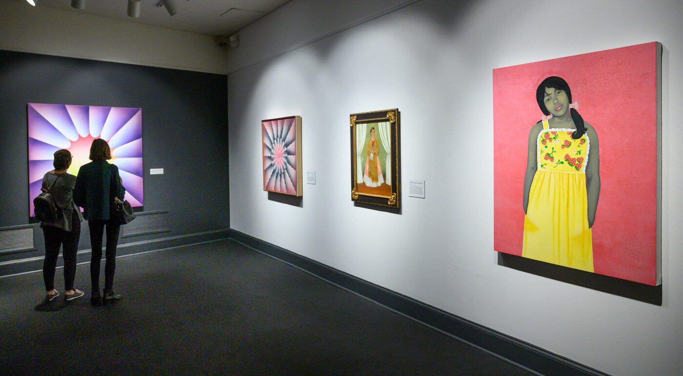 A partial view of an art gallery with four artworks on display, including a painted portrait of a young, pony-tailed medium-dark skinned girl in a yellow flowered dress against a pink background.
