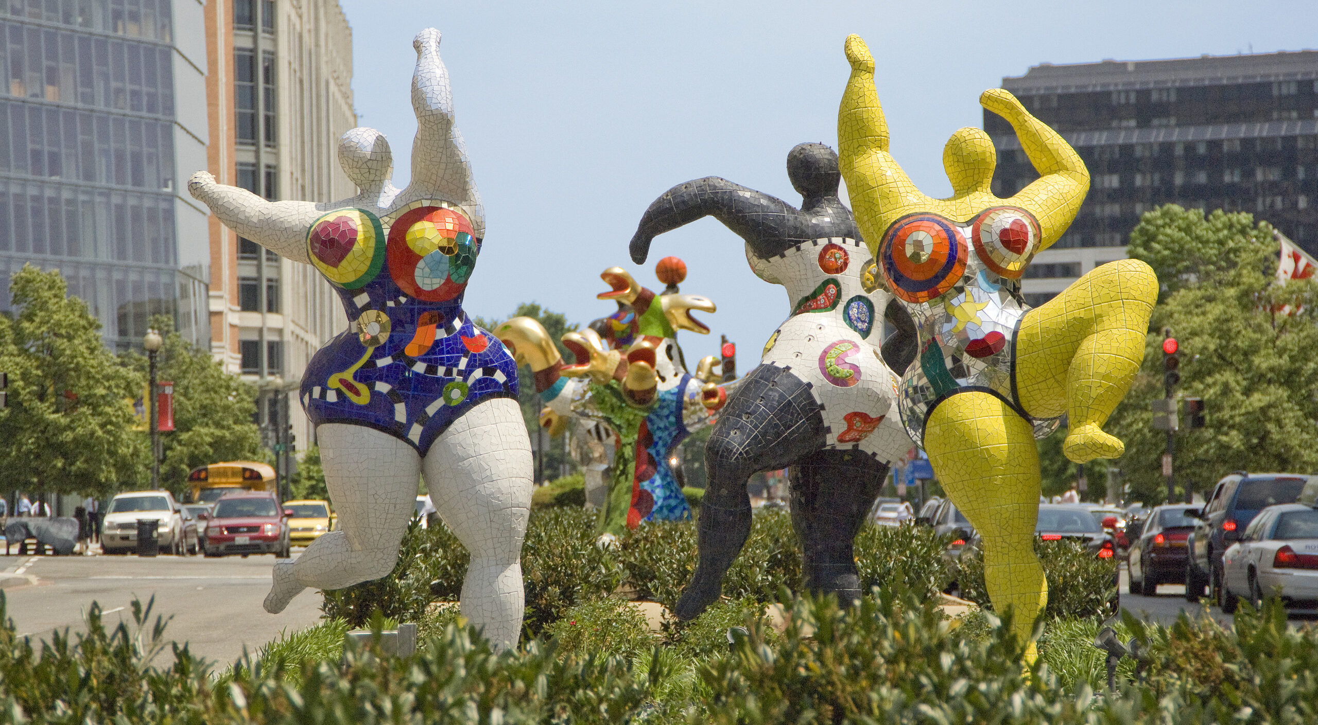 Three abstract outdoor sculptures of voluptuous figures covered in bright patterns and dancing with outstretched arms.