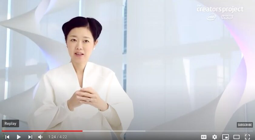 Screenshot of a Youtube video showing a young Japanese woman speaking in a white billowy jumpsuit