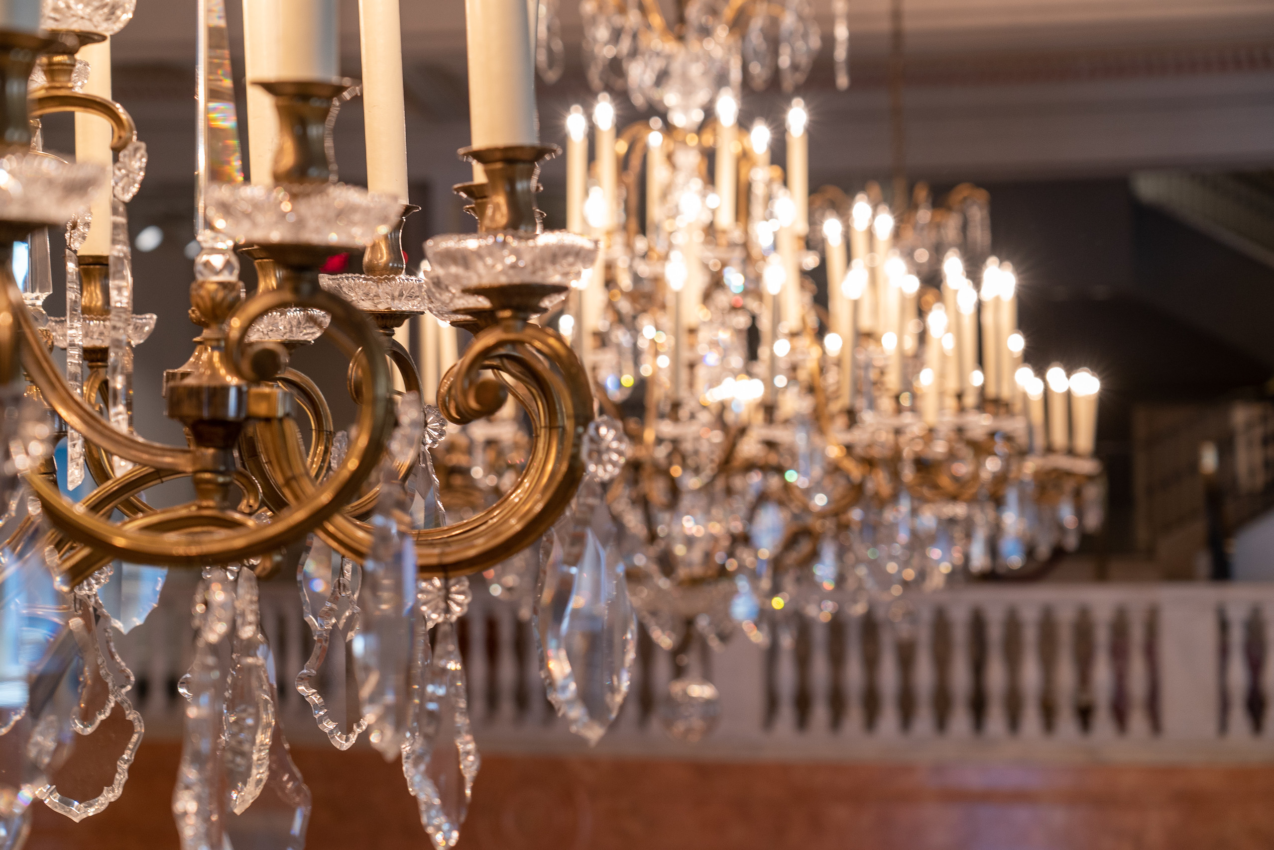 Close-up view of ornate gold and crystal chandeliers in the museum's Great Hall. The camera is focused on the chandelier in the foreground and the rest is out of focus.