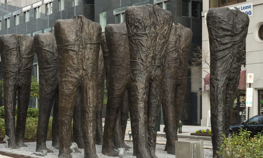 Ten larger-than-life bronze sculptures of human bodies are installed in the middle of a city street. The bodies have no heads or arms, and are striding forward in five rows of two. While they are not naked, their wrinkled body-tight clothing makes no distinction between shirt and pants.
