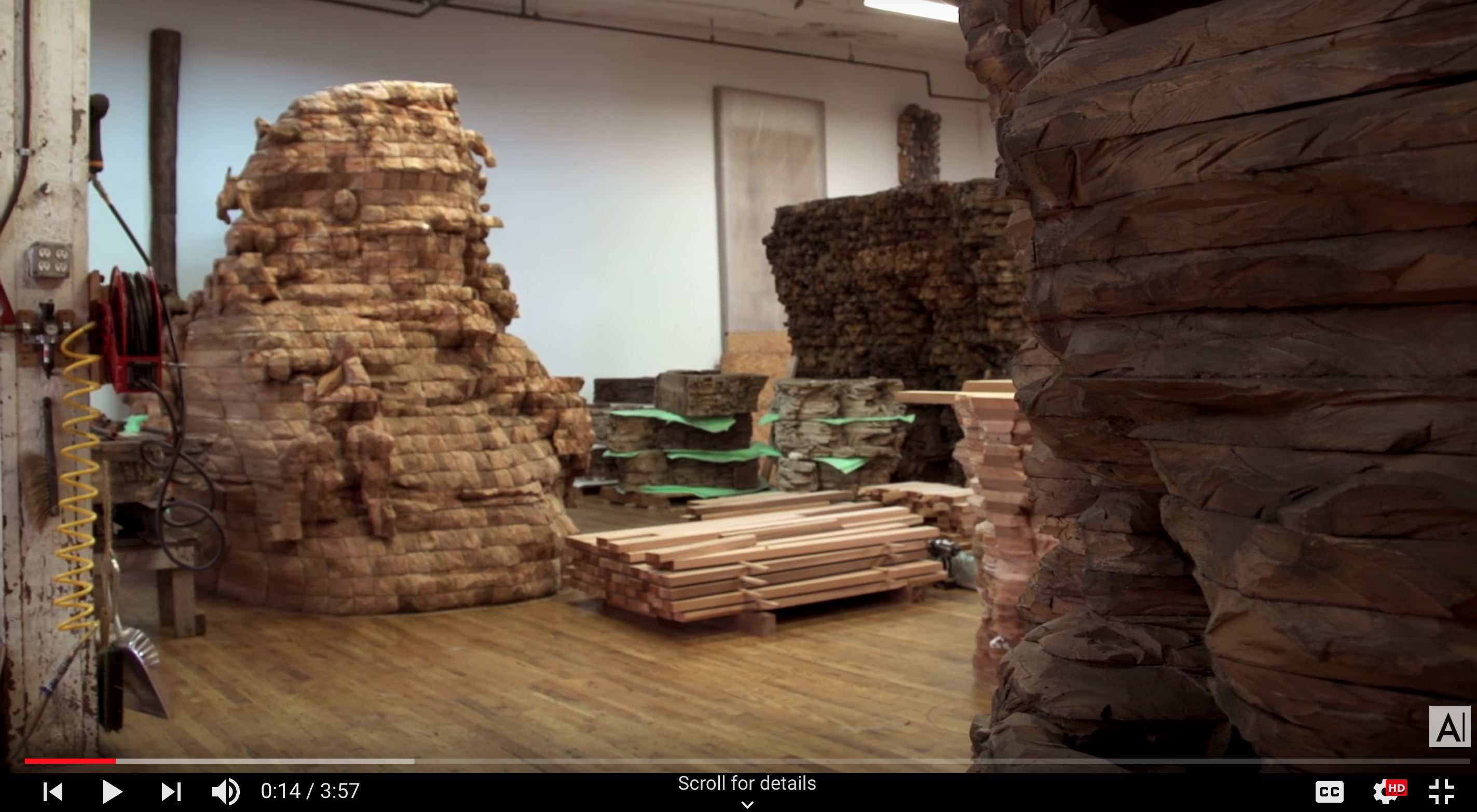 Still image from video about Ursula von Rydingsvard shows a large room with large cedar sculptures.