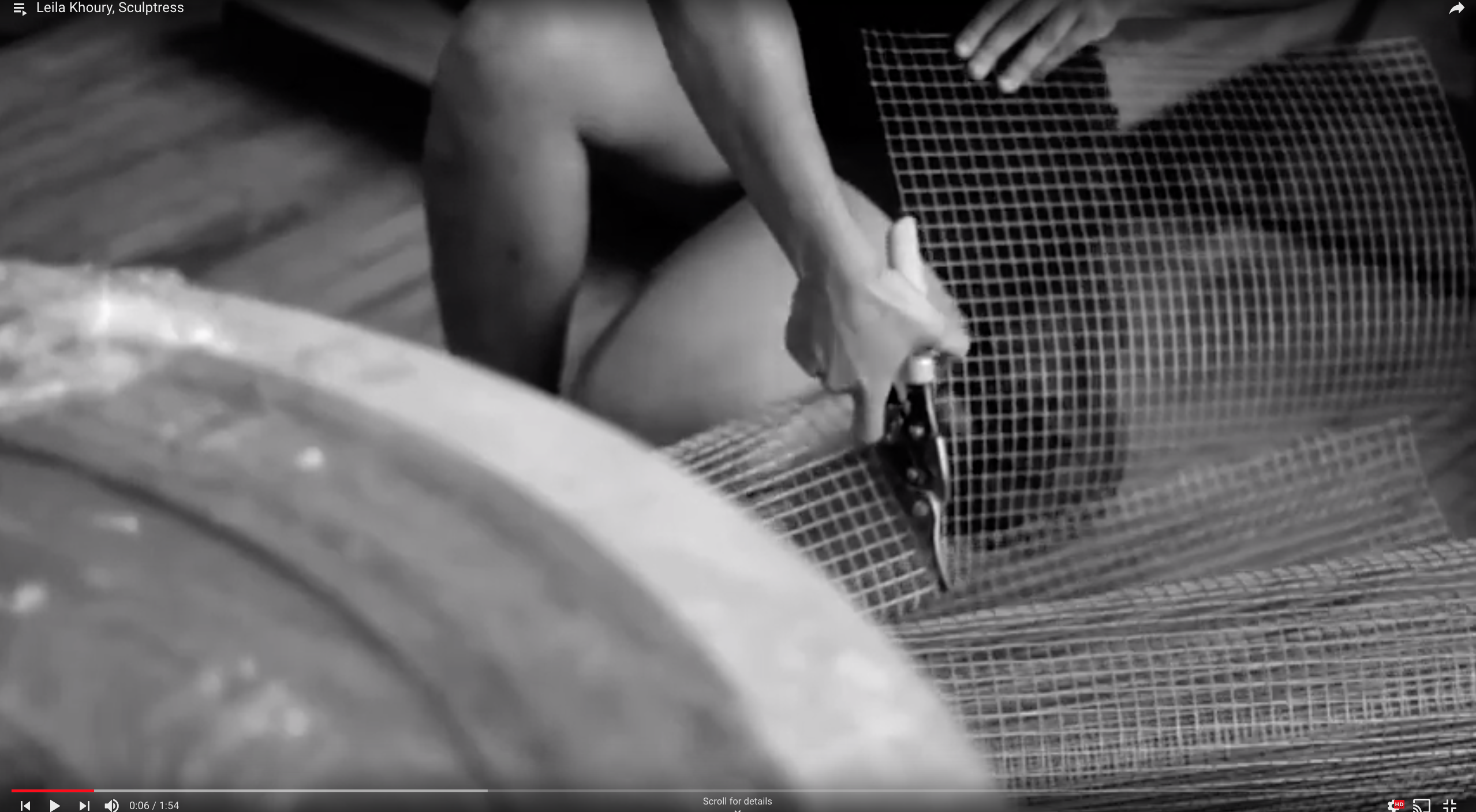 Black and white still image from a video on Leila Khoury shows the artist cutting chicken wire with clippers.