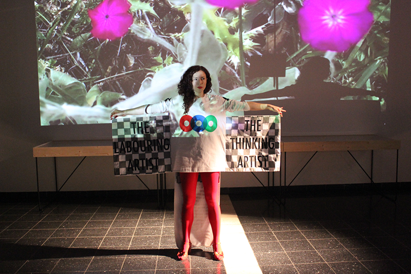 A woman stands in front of a screen projection of purple flowers. She wears red rights and heels and a white T-shirt with three colored disks printed across the center. She holds her arms out to hold two pieces of checkered fabric that extend like wings from her back.