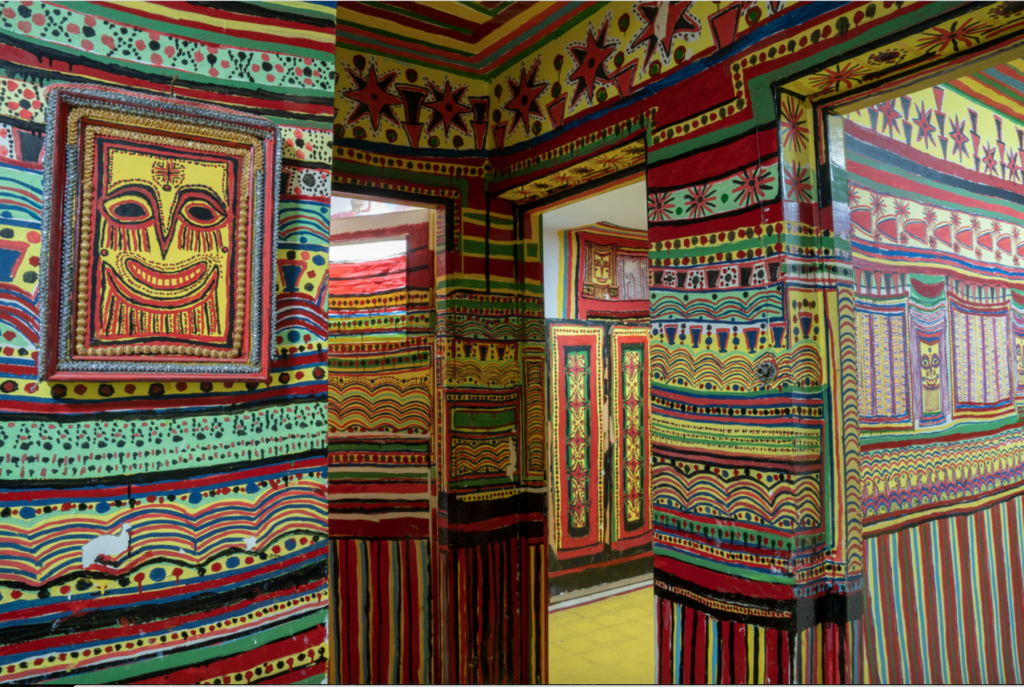 An interior photograph of a home. The walls are mostly red, yellow, green, and blue; vertical stripes ascend the walls until waist height, where horizontal registers of stripes, dots, and scalloped patterns take over. The upper third of the walls are painted in varied repeating shapes like stars and triangles.