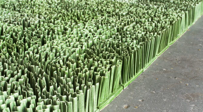 Detail photograph of ceramic sculpture made to look like a patch of lawn. Individual squares consisting of multiple upright blades of porcelain grass, glazed green, fit together to form a lush rectangular field of grass.