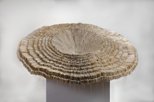 A beige contemporary sculpture with layers of finely cut paper stacked on top of one another getting more expansive with the bottom layers. The flexible edges of the sculpture droop and flop.