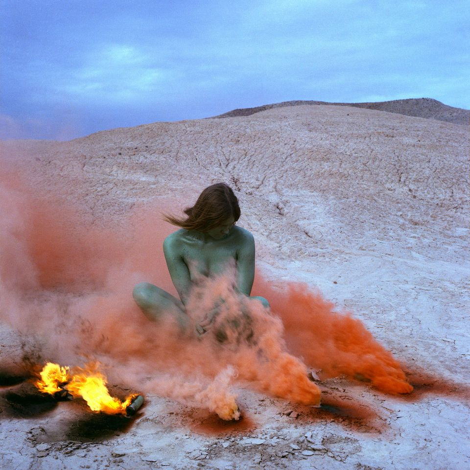 A naked woman with painted forest green skin sits cross-legged in the middle of a desert. She looks down in the direction of red smoke that billows from three locations on the ground to her left; the smoke partially obscures her body. To her right, two flames scorch the ground.