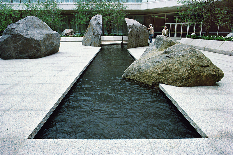 A long, rectangular water pool is cut out of a grey terrazzo tiled courtyard. One large granite rock dips into the pool; at the other end, the water cuts through the middle of another rock, creating glossy vertical edges. Other granite rocks rest throughout the courtyard.