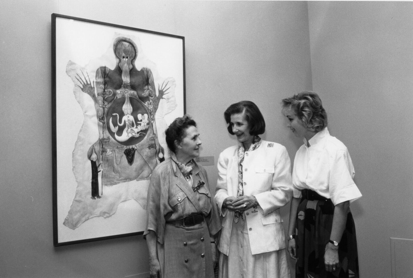 Black and white photograph of three light skinned women casually chatting next to a painting.