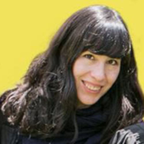 A photograph of an adult woman long, straight, dark hair and thick bangs covering her forehead. She is posed from the neck up against a bright yellow background. She makes eye contact with the viewer and is smiling.